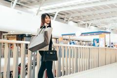 有购物袋的愉快的美丽的妇女在商店站立 有购买的可爱的亚裔妇女在大购物中心请求 库存照片