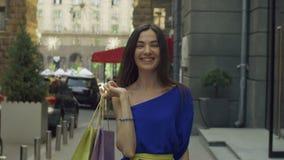 有购物袋的端庄的妇女走在街道上的 影视素材