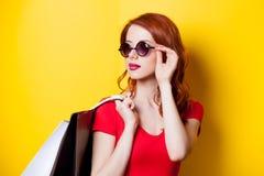 有购物袋的红头发人妇女 免版税库存照片