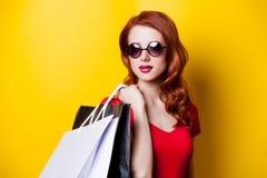 有购物袋的红头发人妇女 免版税图库摄影