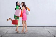 有购物袋站立的愉快的两个亚洲人妇女 免版税库存照片