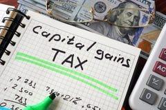 有资本收益税标志的笔记本在桌上 免版税库存图片