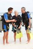 有资深的夫妇与辅导员的佩戴水肺的潜水教训 免版税库存照片