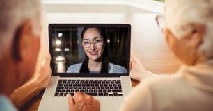 有资深的夫妇背面图与妇女的电视电话会议膝上型计算机的 免版税图库摄影