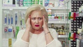 有资深的妇女头疼,寻找医学在药房 股票录像