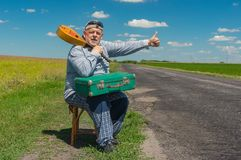 有资深的旅行者农村路旁的短的基于与古老绿色手提箱和曼陀林 免版税图库摄影