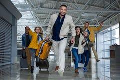 有赛跑在机场的行李的高兴的伴侣 免版税库存图片