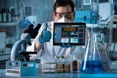有赞许和拿着的数字式片剂研究员有屏幕的 库存照片