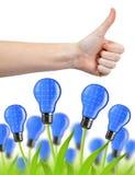 有赞许和eco能量电灯泡的手 免版税库存图片