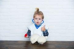 有赞许姿态的孩子兽医医生诊断玩具熊 免版税库存照片