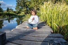 有赤脚的平安的美丽的瑜伽孩子在安静的水附近 库存图片