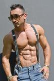 有赤裸上身的悬挂装置的英俊,肌肉爱好健美者 图库摄影