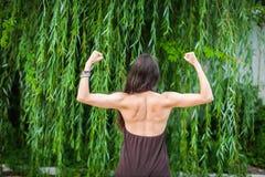 有赤裸后面的美丽的妇女在绿色垂柳背景 体育女孩展示背部肌肉 免版税库存图片