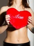 有赤裸身体的年轻美丽的女孩,拿着一个红色心脏枕头 库存照片