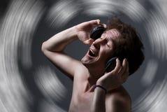 有赤裸躯干的一个人听到与耳机的音乐的 免版税库存图片