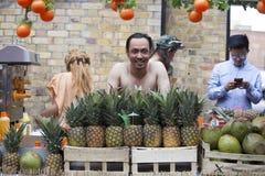 有赤裸躯干的人卖在砖车道的椰子 图库摄影