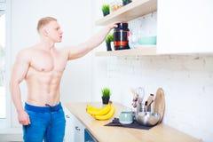 有赤裸躯干的肌肉人在有体育营养蛋白质和香蕉的,概念厨房里的健康 图库摄影