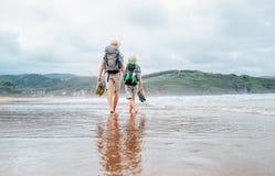 有赤足儿子步行的父亲在沙子海洋海滩 库存照片