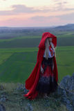 有赤足站立在w的红色斗篷的美丽的白肤金发的妇女 库存图片