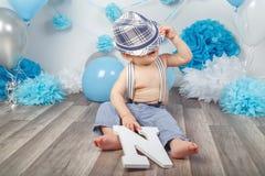 有赤足蓝眼睛的男婴在有悬挂装置的裤子,被盖掩藏在帽子下,坐木地板在演播室 库存图片