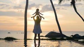 有走和使用在海滩的孩子的女孩在日落期间 家庭休闲 影视素材