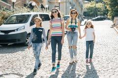 有走在一条城市街道上的孩子的成熟妇女在夏天好日子 免版税库存图片