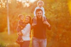 有走在公园的孩子的年轻家庭 父亲、母亲和两个儿子 免版税库存照片