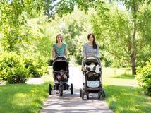 有走在公园的婴儿车的母亲 库存图片