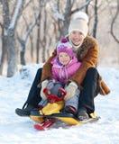 有走在冬天公园的子项的母亲 免版税库存照片