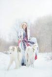 有走在冬天的两灵狮的女孩 免版税库存照片