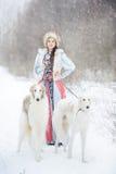 有走在冬天的两灵狮的女孩 免版税库存图片