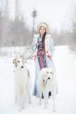 有走在冬天的两灵狮的女孩 库存照片