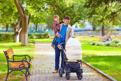 有走在城市公园的孩子的父亲 免版税库存照片