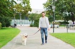 有走在城市的拉布拉多狗的愉快的人 免版税库存照片
