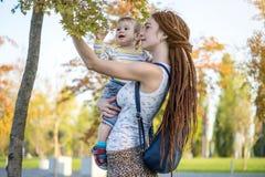 有走在晴朗的公园的小儿子的年轻现代妈妈 母性喜悦的概念  库存照片