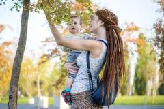 有走在晴朗的公园的小儿子的年轻现代妈妈 母性喜悦的概念  库存图片