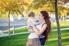 有走在晴朗的公园的小儿子的年轻现代愉快的妈妈 概念母性和秋天心情 库存图片