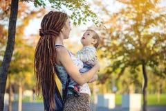 有走在晴朗的公园的小儿子的年轻现代愉快的妈妈 概念母性和秋天心情 库存照片