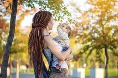 有走在晴朗的公园的小儿子的年轻现代愉快的妈妈 概念母性和秋天心情 图库摄影