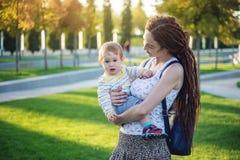 有走在晴朗的公园的小儿子的年轻现代愉快的妈妈 母性和秋天心情喜悦的概念  图库摄影