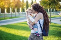 有走在晴朗的公园的小儿子的年轻现代愉快的妈妈 母性和秋天心情喜悦的概念  库存照片