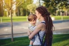 有走在晴朗的公园的小儿子的年轻现代愉快的妈妈 母性和秋天心情喜悦的概念  库存图片