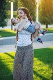 有走在晴朗的公园的小儿子的年轻现代愉快的妈妈 母性和秋天心情喜悦  库存照片