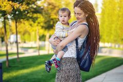 有走在晴朗的公园的小儿子的年轻现代愉快的妈妈 母性和秋天心情喜悦  库存图片