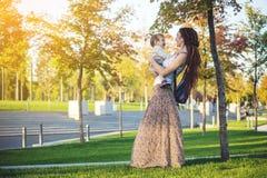 有走在晴朗的公园的小儿子的年轻现代愉快的妈妈 母性和秋天心情 库存图片