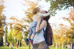 有走在晴朗的公园的小儿子的年轻现代愉快的妈妈 母性和秋天心情 库存照片