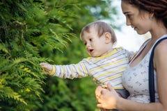 有走在晴朗的公园的小儿子的年轻现代愉快的妈妈 母性喜悦的概念  库存照片