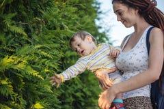 有走在晴朗的公园的小儿子的年轻现代愉快的妈妈 母性喜悦的概念  图库摄影