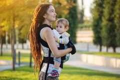 有走在晴朗的公园的小儿子的年轻现代愉快的妈妈 母性喜悦的概念  库存图片
