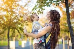 有走在晴朗的公园的小儿子的现代愉快的妈妈 母性和秋天心情喜悦  库存图片